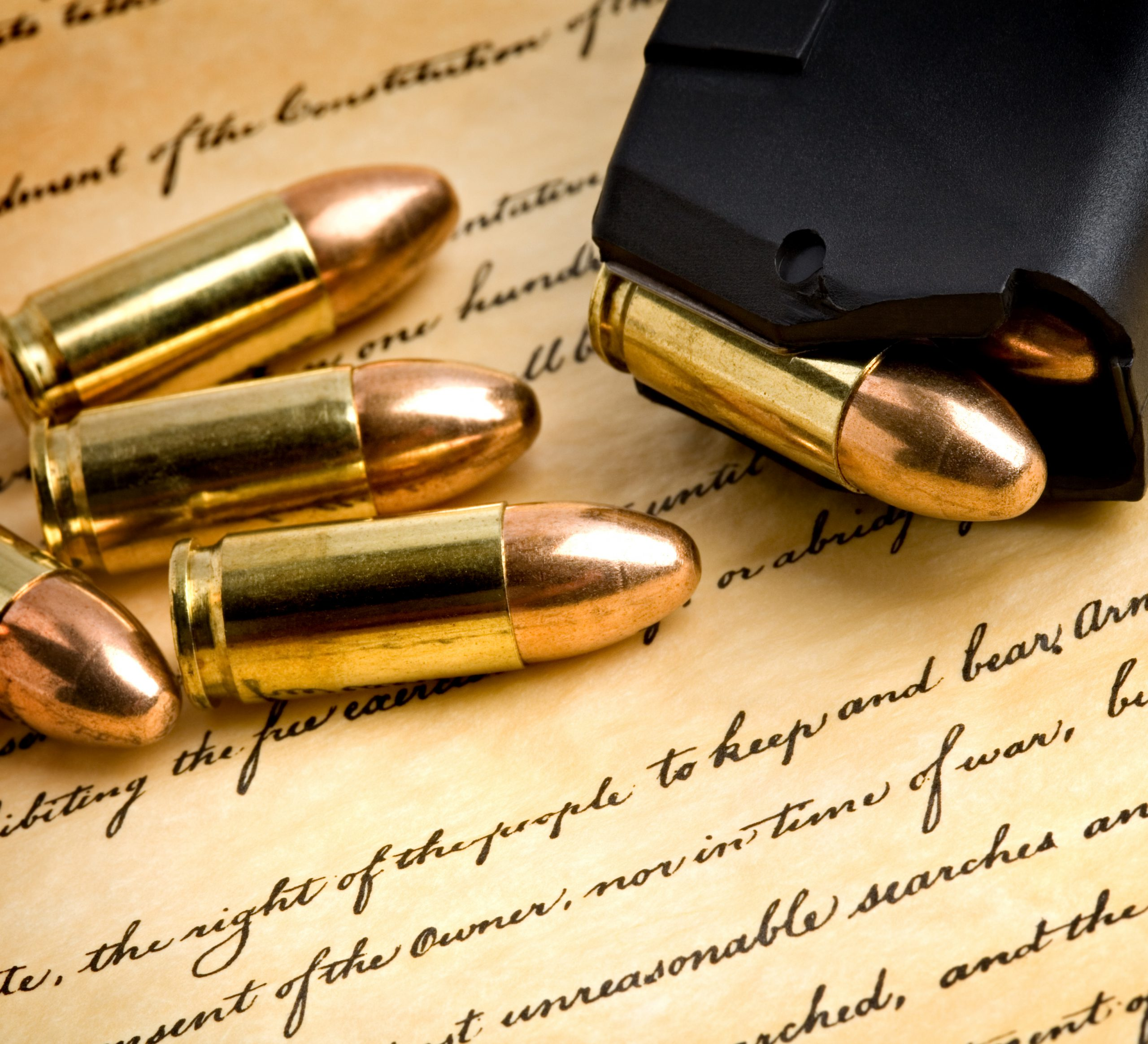 Gold and copper bullets with clip on top of a document